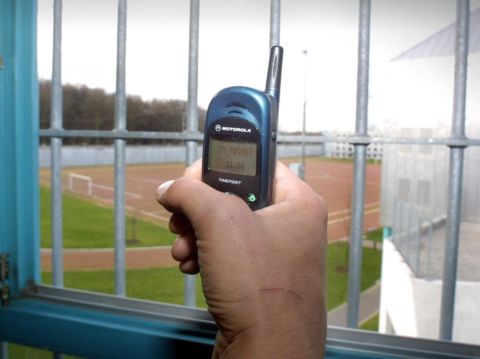 Un preso muestra un teléfono móvil dentro de una celda de una cárcel alemana.