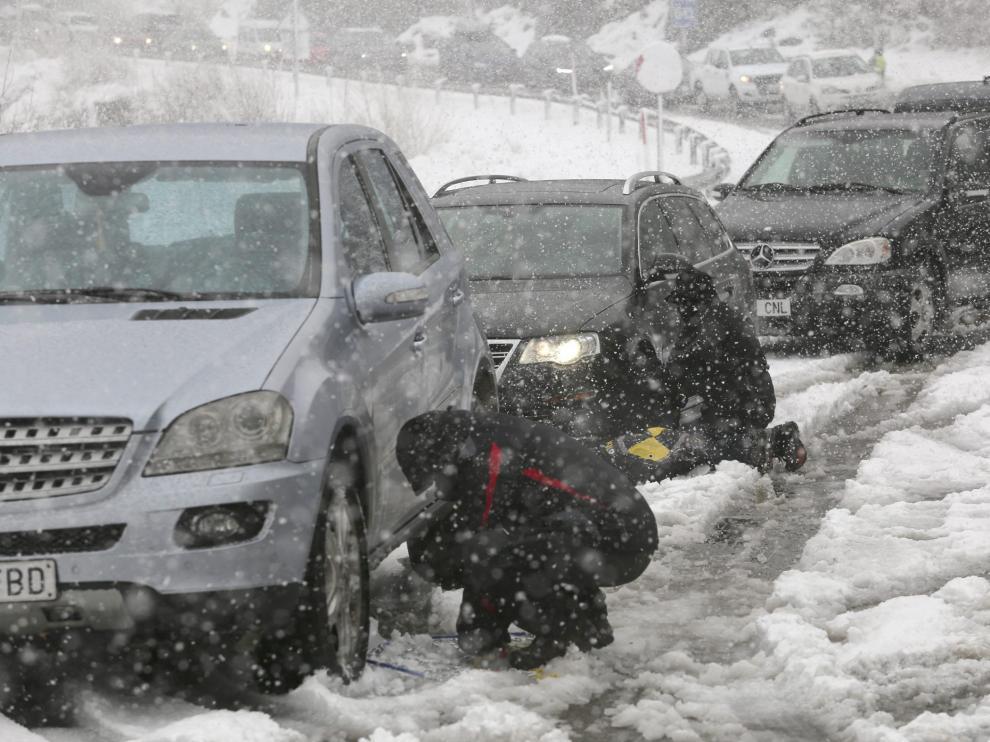 Conductores colocando cadenas en sus vehículos este sábado por la mañana a la altura de Santa Elena, en la carretera de Biescas.
