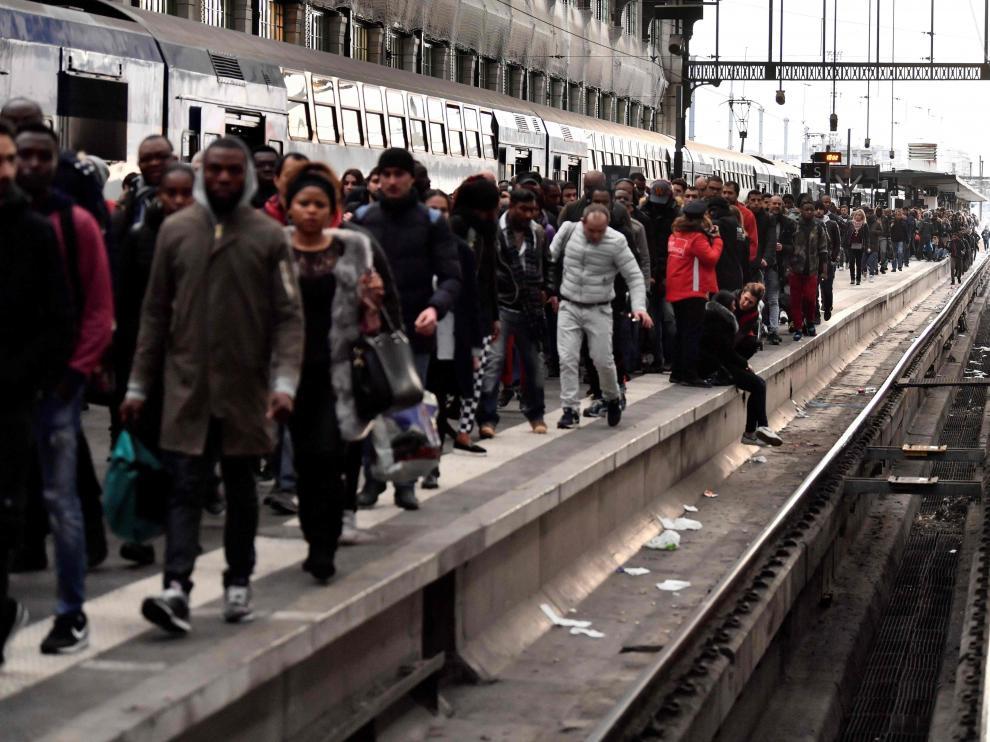 Los pasajeros esperan sentados o caminando por las vías en el primer día de huelga ferroviaria
