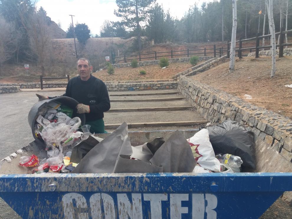 Un trabajador de Atadi recoge la basura desperdigada por Fuente Cerrada.