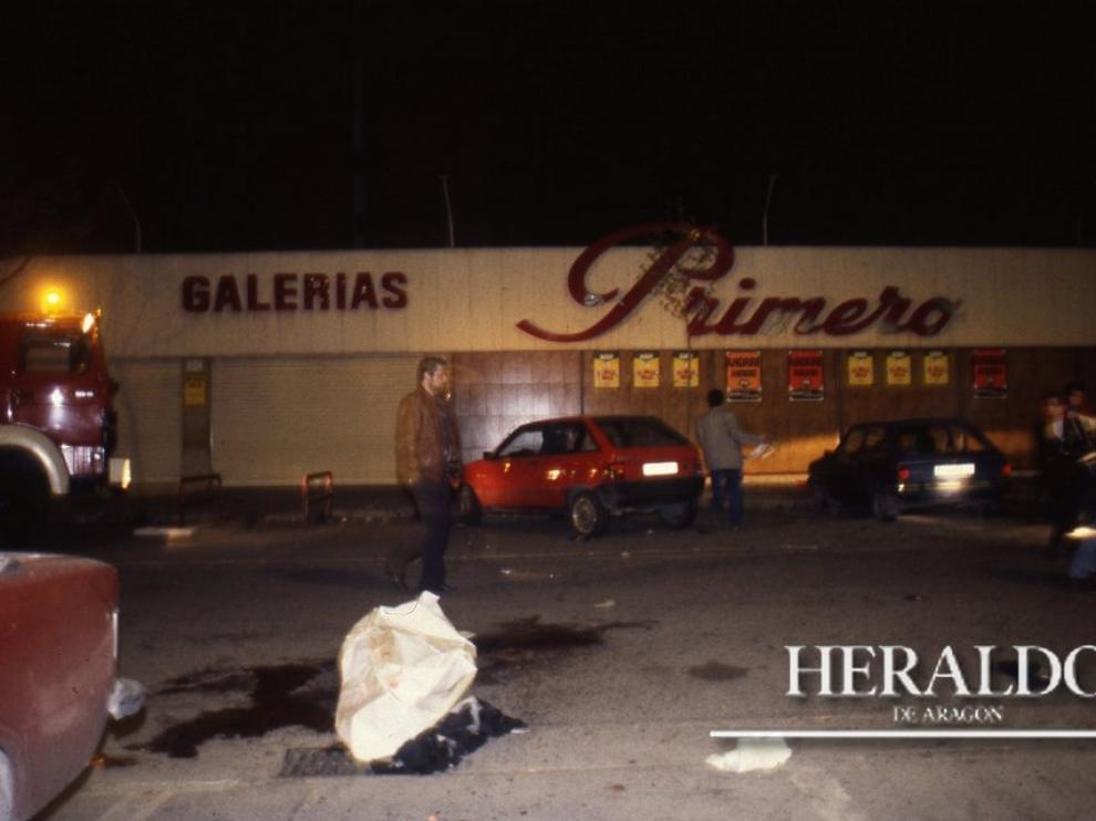 Uno de los cadáveres yace entre manchas de sangre en el lugar del atentado terrorista de los Grapo a un furgón de Prosegur frente a la fachada de Galerías Primero ubicado en el barrio zaragozano de Monsalud, el 7 de abril de 1993.