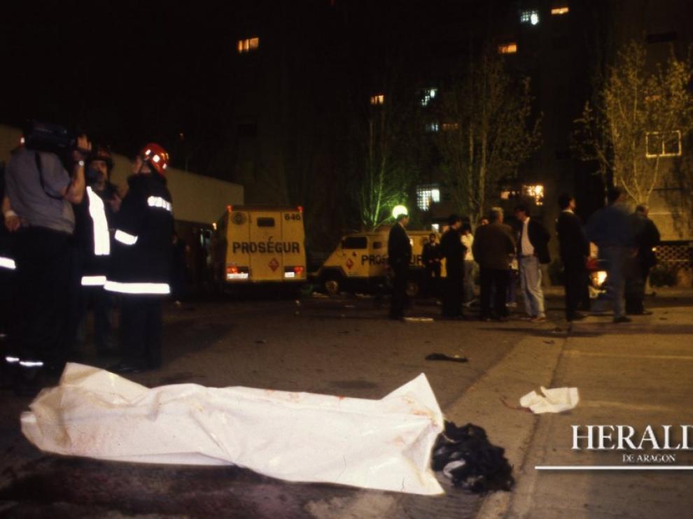 Uno de los cadáveres yace entre manchas de sangre en el lugar del atentado terrorista frente a la fachada de Galerías Primero ubicado en el barrio zaragozano de Monsalud, el 7 de abril de 1993.