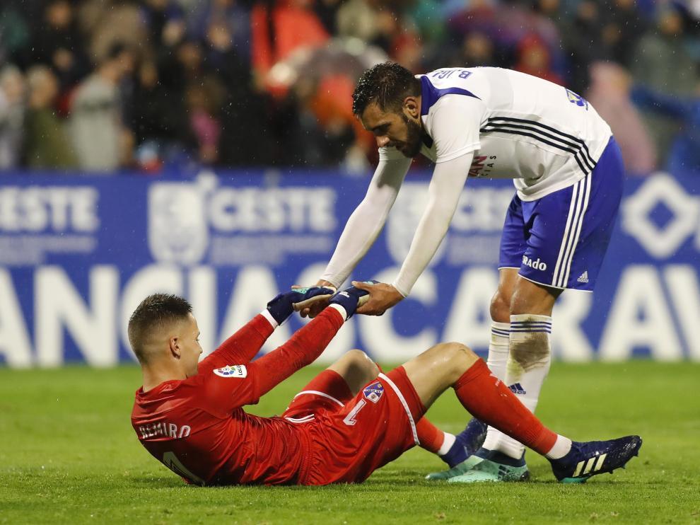 Borja Iglesias, delantero del Real Zaragoza, ayuda a Álex Remiro, portero del Huesca, en el último derbi aragonés.