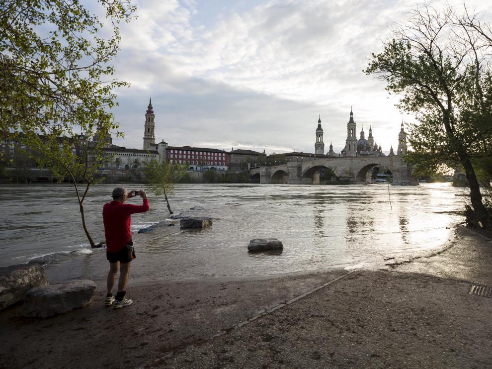 Un zaragozano fotografía el caudal del Ebro a su paso por Zaragoza