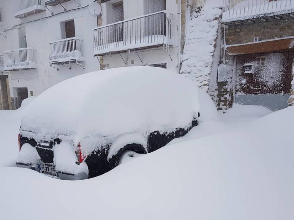 Un coche, cubierto de nieve este jueves, 12 de abril, en una calle de Valdelinares.