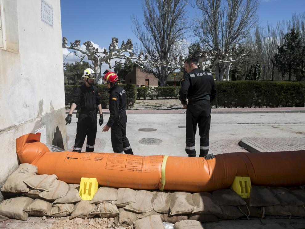 Un vecino de Novillas sortea unas de las barreras de contención que la UME colocó el viernes en la localidad para evitar que el agua entrara en el casco urbano.