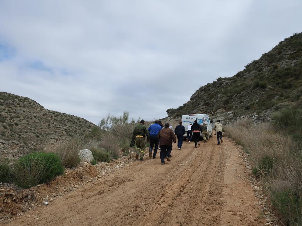 El alcalde, varios vecinos y los agentes ayudan a empujar una furgoneta atascada.