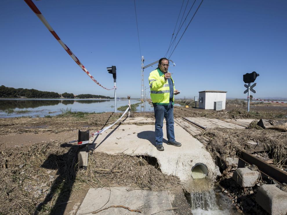 Un operario del ADIF, ayer, evaluando los daños que la avenida del Ebro ha causado en la línea ferroviaria Zaragoza-Reus.
