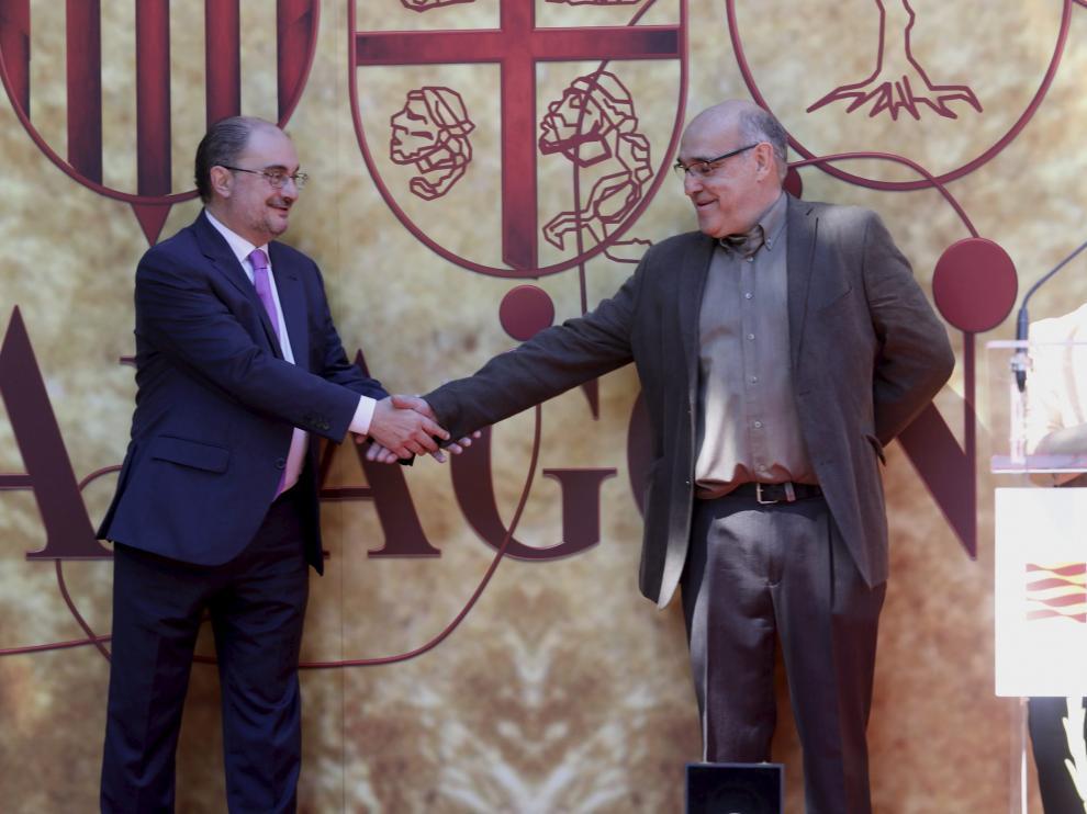 Javier Lambán da la mano a Paco Paricio mientras Pilar Amorós agradece la medalla concedida.