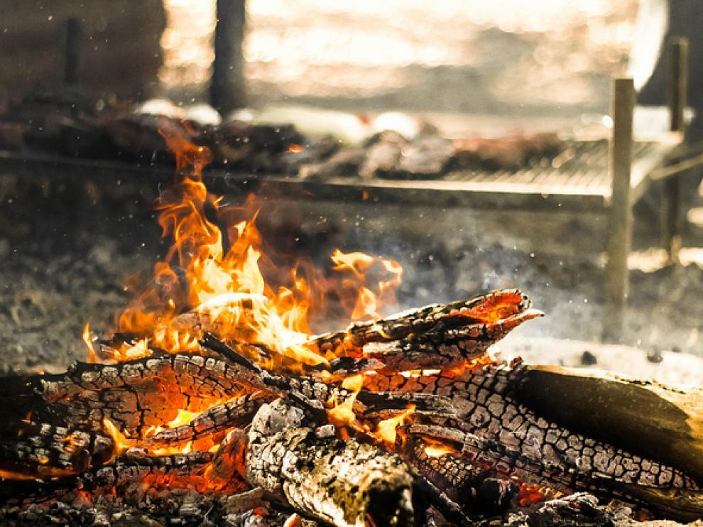Cocinar sobre un fuego de leña humeante deposita HPA de la leña en la carne