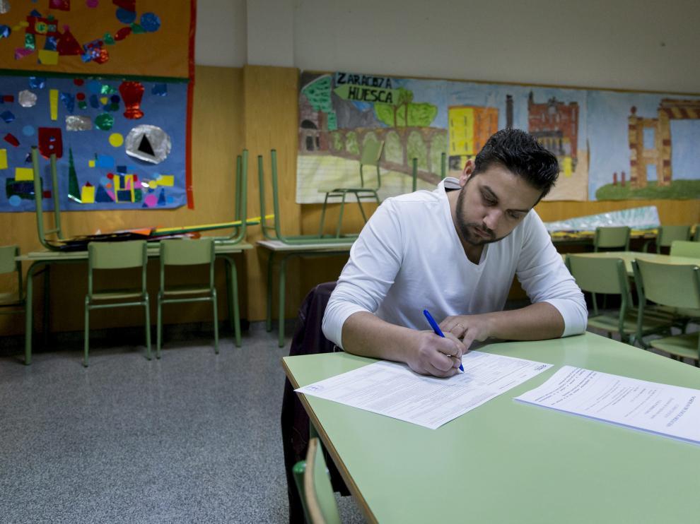 Juan Clavería rellena la solicitud de plaza escolar en el aula de psicomotricidad del colegio Parque Goya.