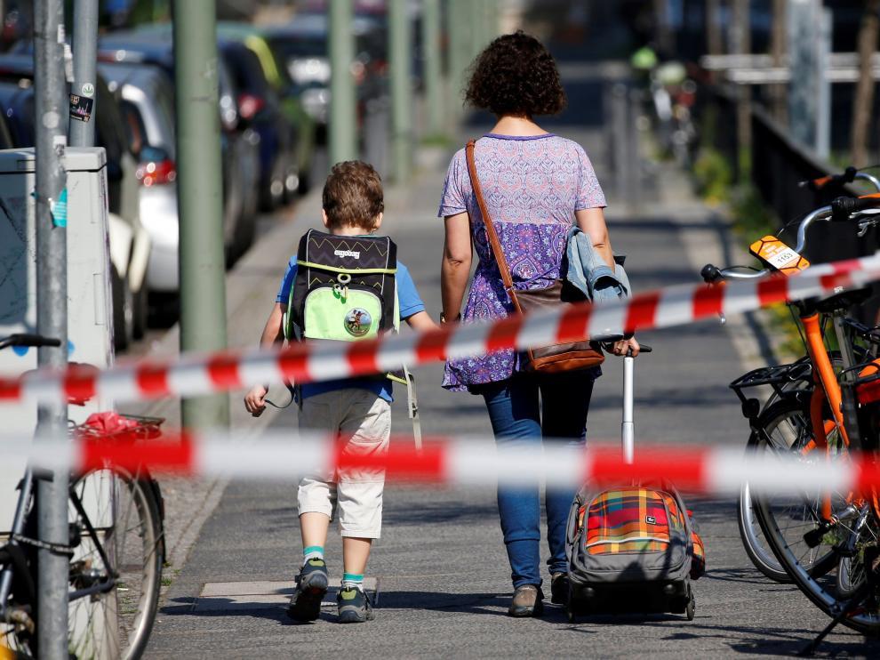 Una mujer y su hijo caminan por una calle acordonada durante la evacuación de resientes en Berlín
