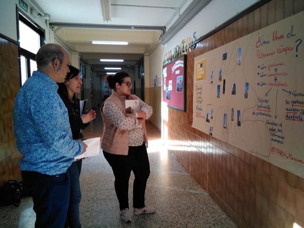 El director del instituto y dos técnicos de Tarazona Monumental frente al mural que recuerda el Día del Patrimonio en el centro escolar