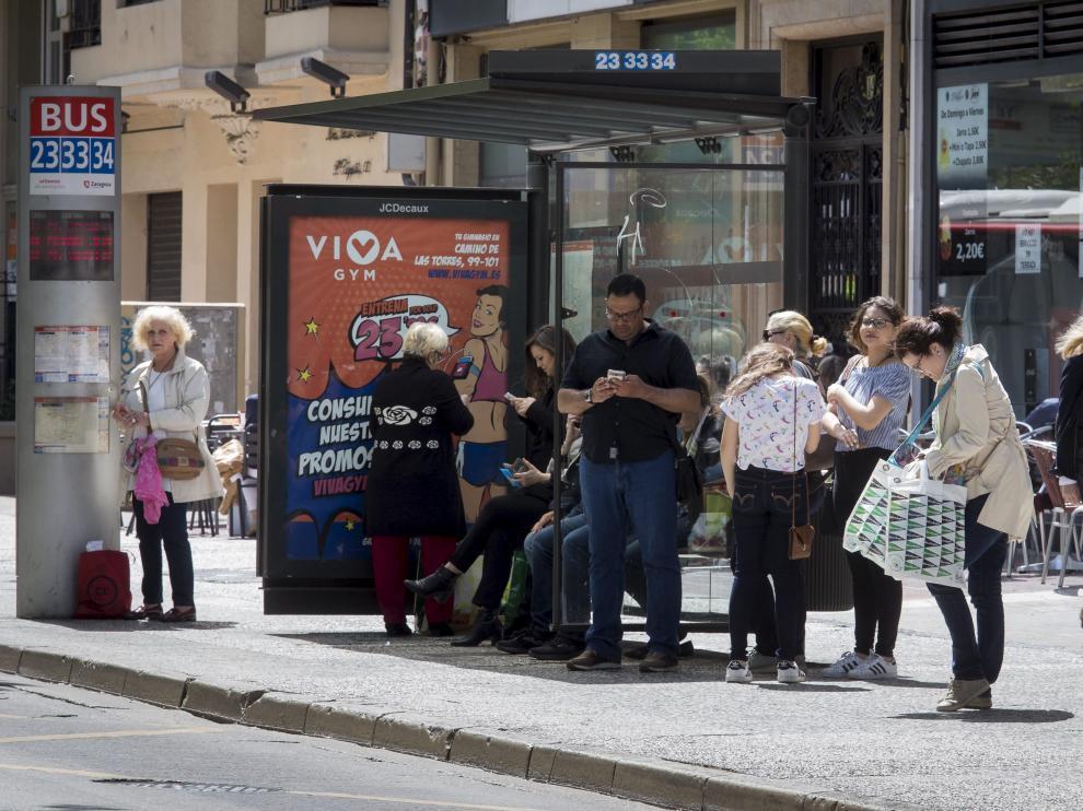 Varios usuarios esperan el autobús en el paseo de Sagasta.