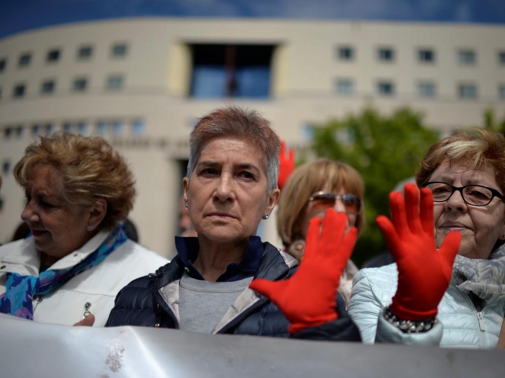 Manifestantes protestan a las puertas de e la Audiencia de Navarra con las manos pintadas de rojo, símbolo contra las agresiones sexistas