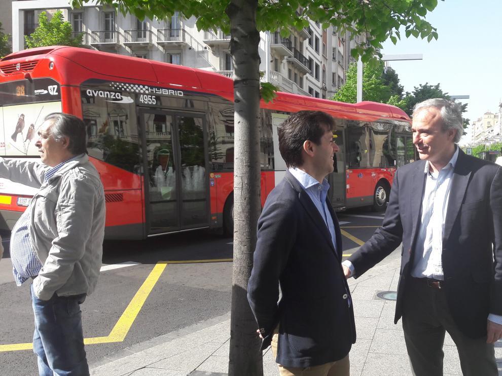 El portavoz del PP, Jorge Azcón, conversa este viernes con el edil de su grupo Sebastián Contín, en la parada del autobús de la plaza de España.