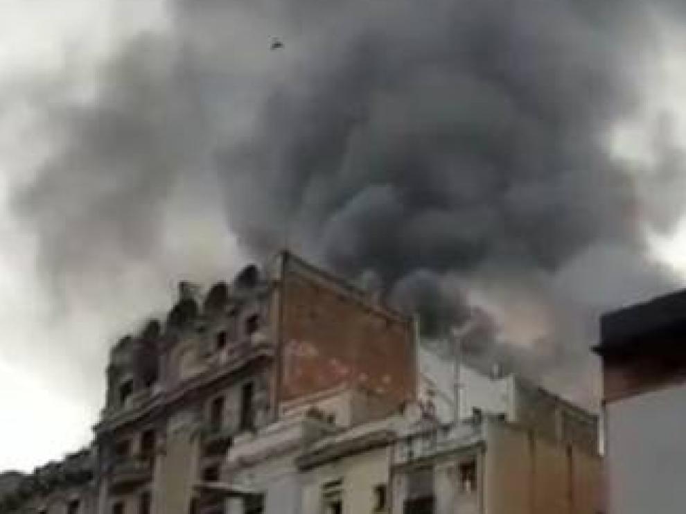 Imagen de la columna de humo provocada por el incendio en un piso del Raval, en Barcelona.