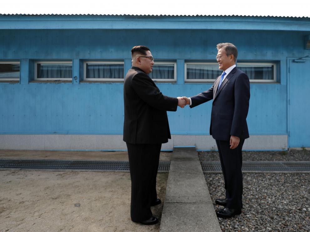 El presidente de Corea del Sur, Moon Jae -in, y el líder norcoreano Kim Jong-un se saludan en la línea de demarcación militar