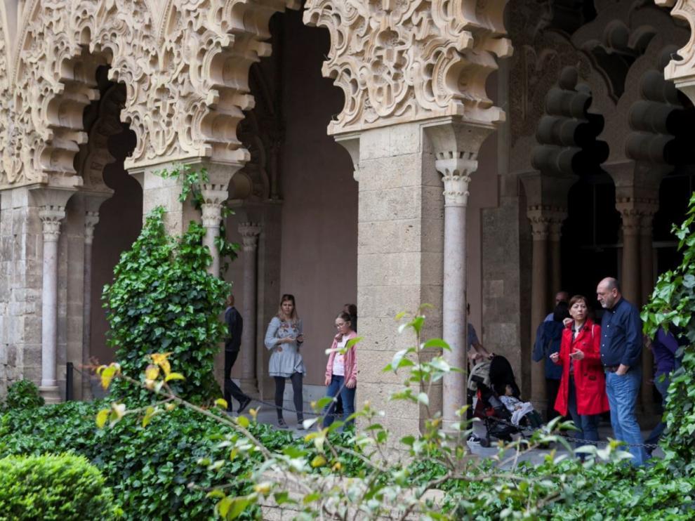 Visitantes bajo los arcos de patio central del palacio de la Aljafería, en Zaragoza.