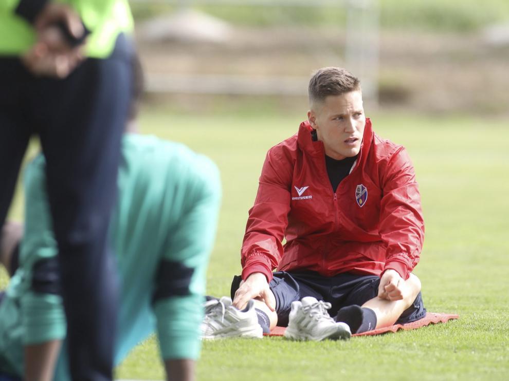 El portero Remiro, sobre el césped del Instituto Montearagón durante el entrenamiento que el Huesca ha completado este domingo tras vencer al Granada.