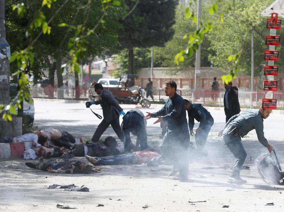 Un policía ayuda a periodistas víctimas de la segunda explosión en Kabul