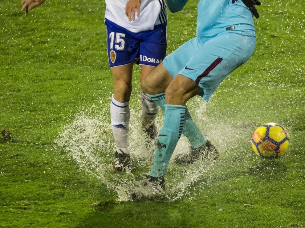Imagen del partido Real Zaragoza-Barcelona B, con el balón y los jugadores atascados en el agua y el barro en la lluviosa noche de enero... en la que el equipo aragonés también se obturó peligrosamente.