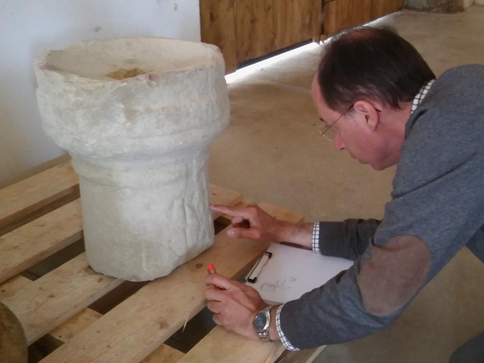 El arqueólogo e historiador Javier Andreu, director de los trabajos en Los Bañales, estudiando la pieza.