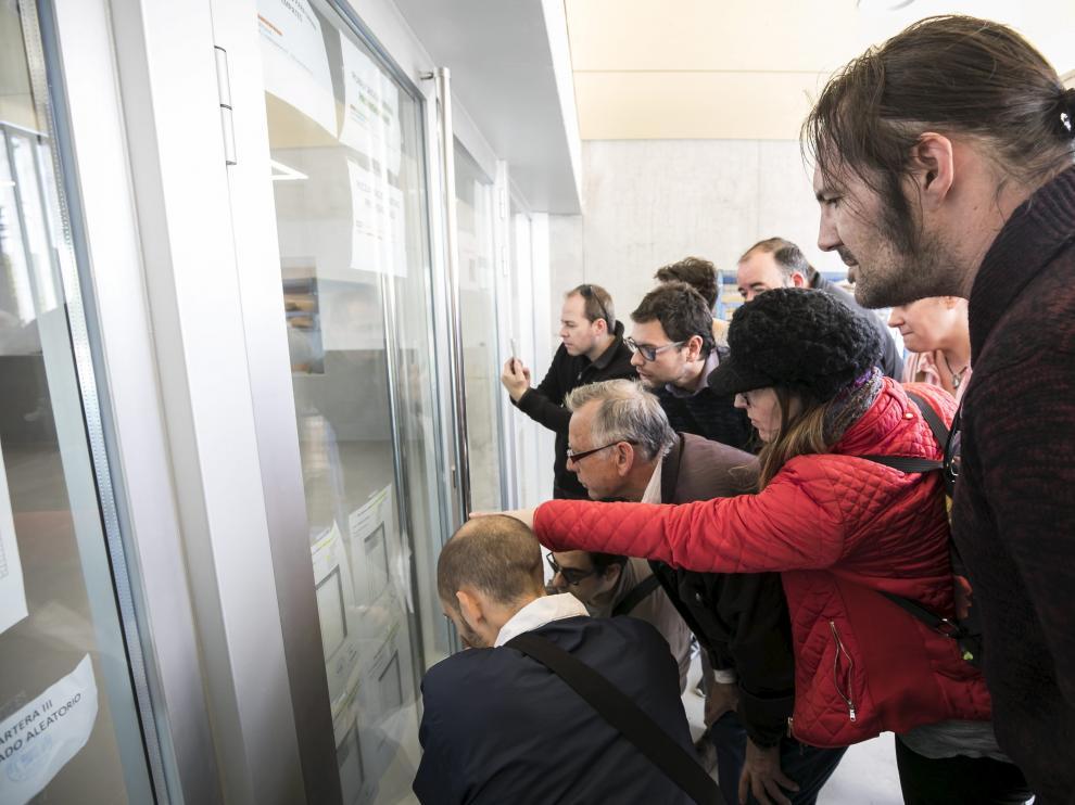 Familiares miran las listas provisionales de admitidos en el colegio Valdespartera III