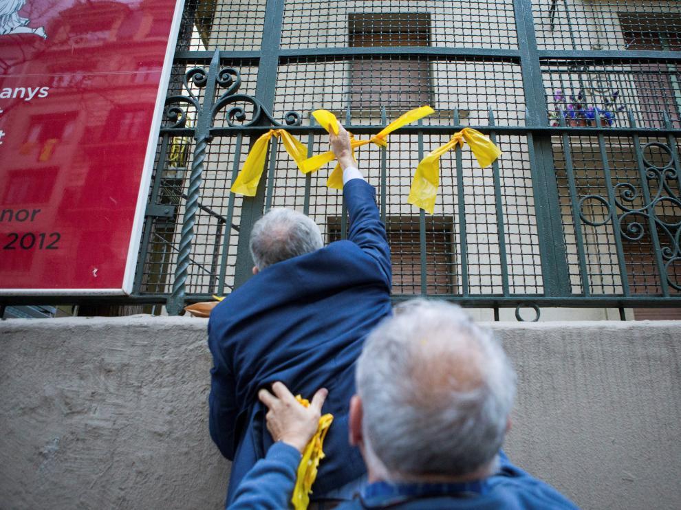 Dos miembros de los GDR retiran lazos amarillos previamente colocados por los CDR.