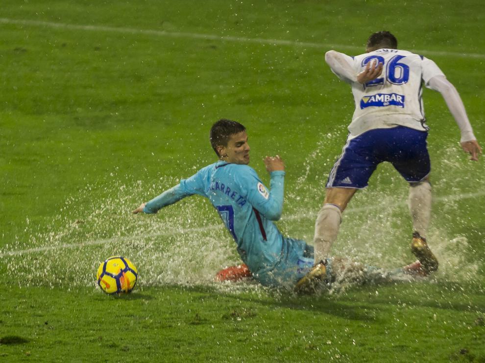Raúl Guti pelea un balón con Ruiz de Galarreta bajo la lluvia, en el partido de ida en La Romareda