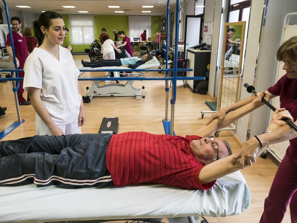 Los enfermos de esclerosis múltiple se ejercitan en el gimnasio de la sede de Fadema.
