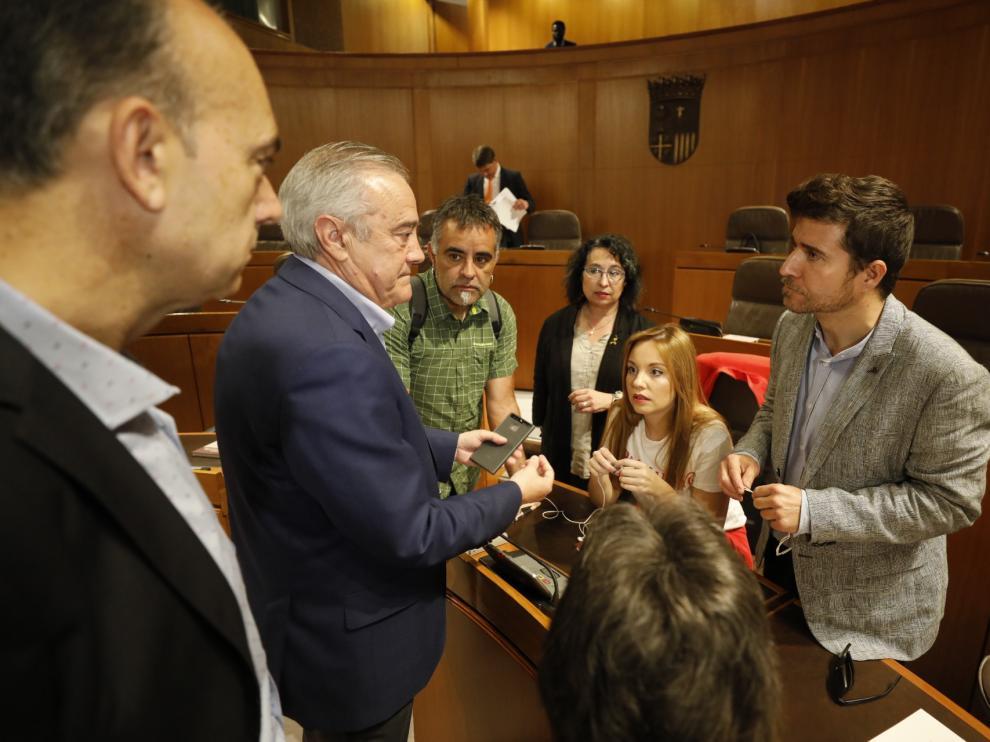 Nacho Escartín, a la derecha, habla con el socialista Javier Sada antes de comenzar el pleno de este jueves