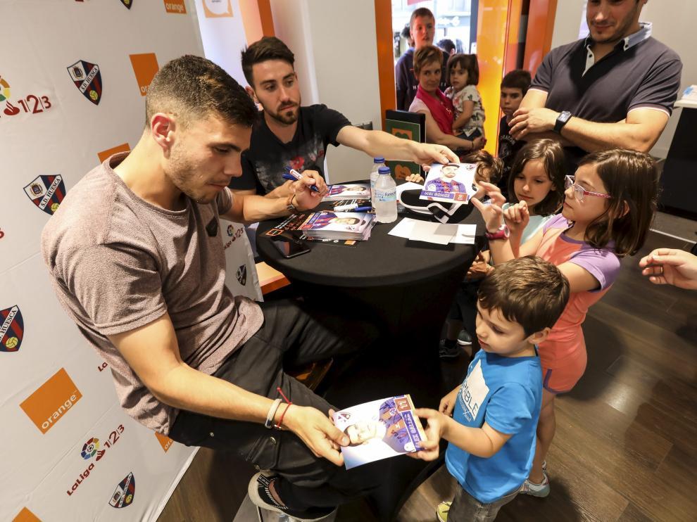 Gallar y Moi Gómez, rodeados de aficionados azulgranas este jueves en la tienda Orange de la capital oscense.