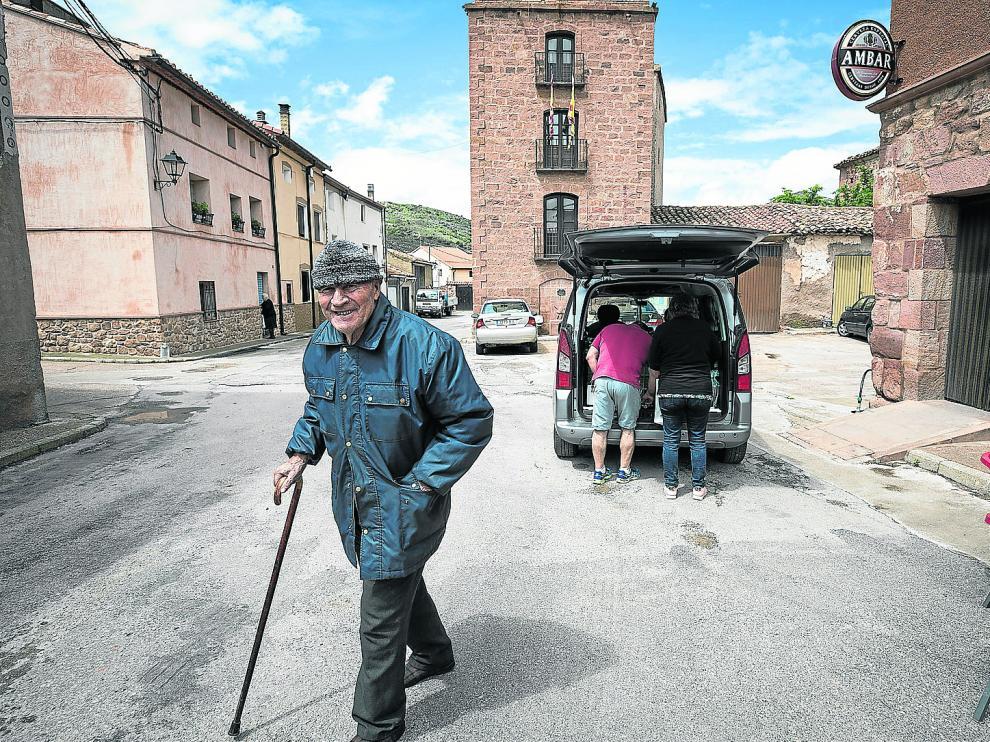 Un vecino de Villar del Salz sonríe a cámara con el ayuntamiento (el más estrecho de la provincia de Teruel) al fondo.