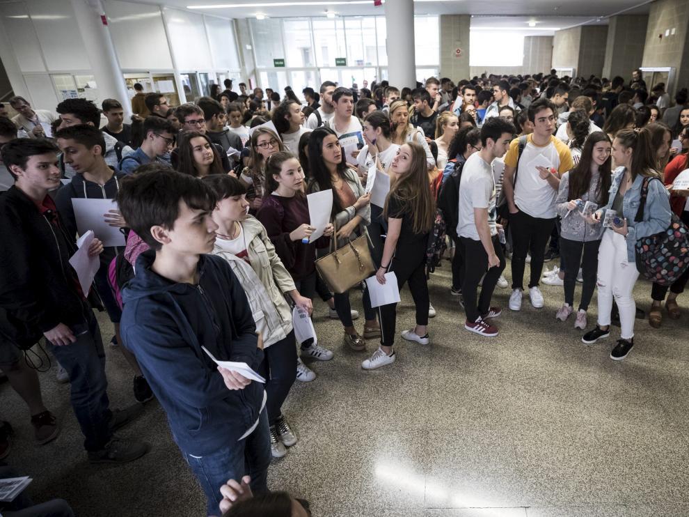 Un grupo de estudiantes esperan para entrar en el aula en la que se examinarán de una de las pruebas de la Evau