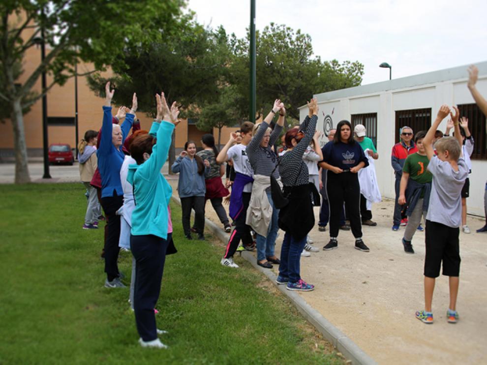 El grupo de paseos saludables y los alumnos del IES El Picarral, frente a la casa del barrio de Parque Goya