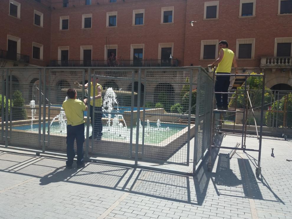 Unos operarios montan las vallas de protección de la fuente de la plaza de San Juan.