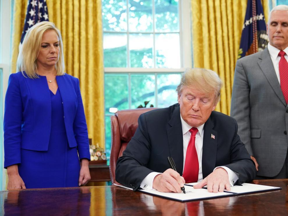 Donald Trump firmando la orden que permitirá a los niños quedarse con sus padres en centros de detención.
