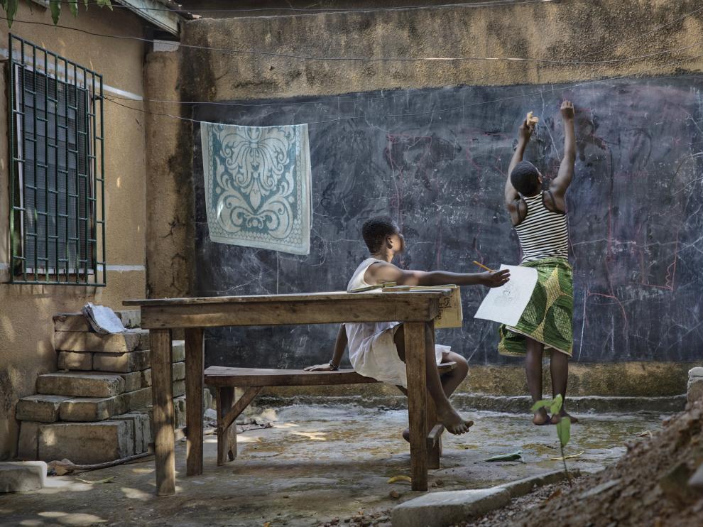 L'Amour y Pagne, de 13 años, hacen sus deberes en la inmensa pizarra del patio.