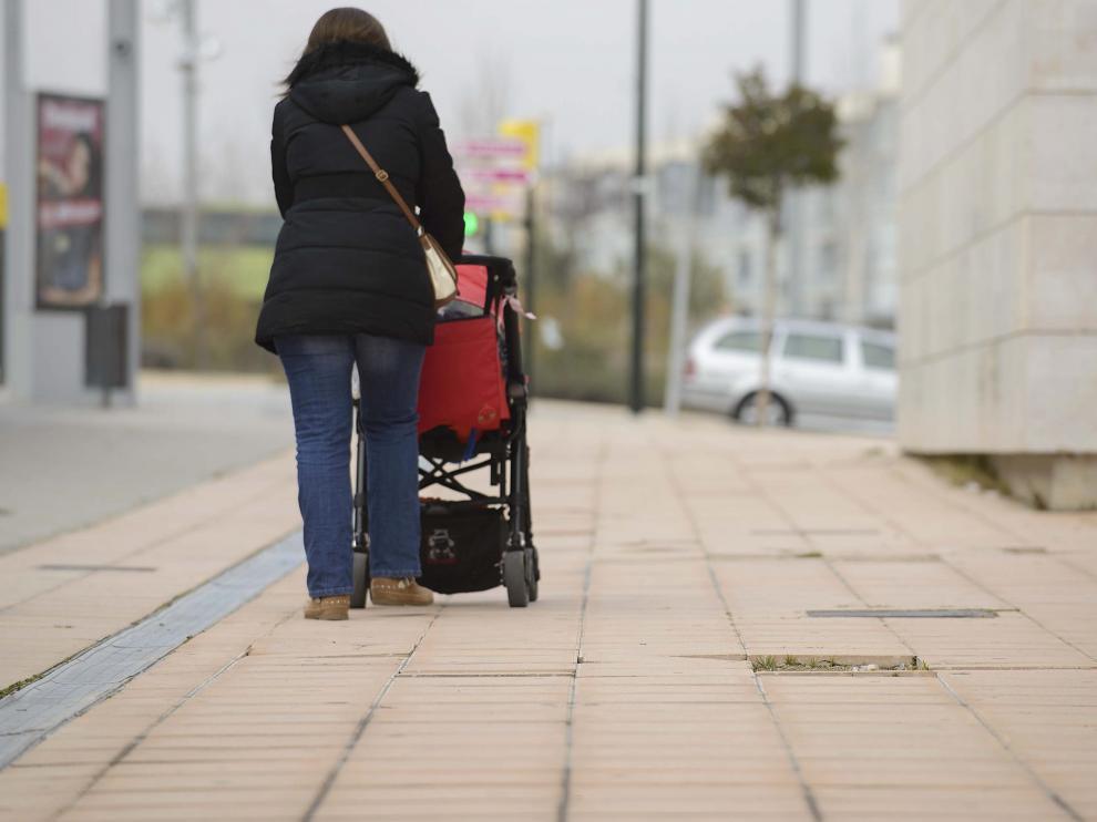 Imagen de archivo de una zaragozana paseando a su hijo.
