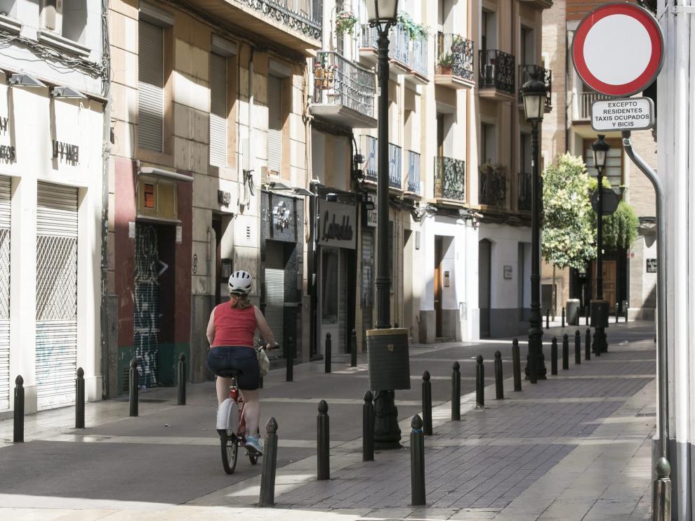 Una ciclista, este martes, a su paso por la calle de Méndez Núñez, junto a una de las señales que permite el acceso de bicicletas y que se retirará en los próximos días.