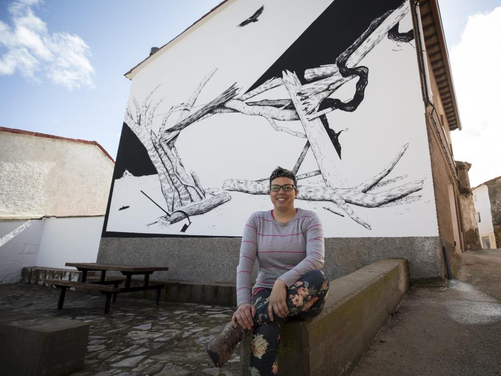 La alcaldesa de Aladrén, frente a uno de los murales que decoran las calles del pueblo.