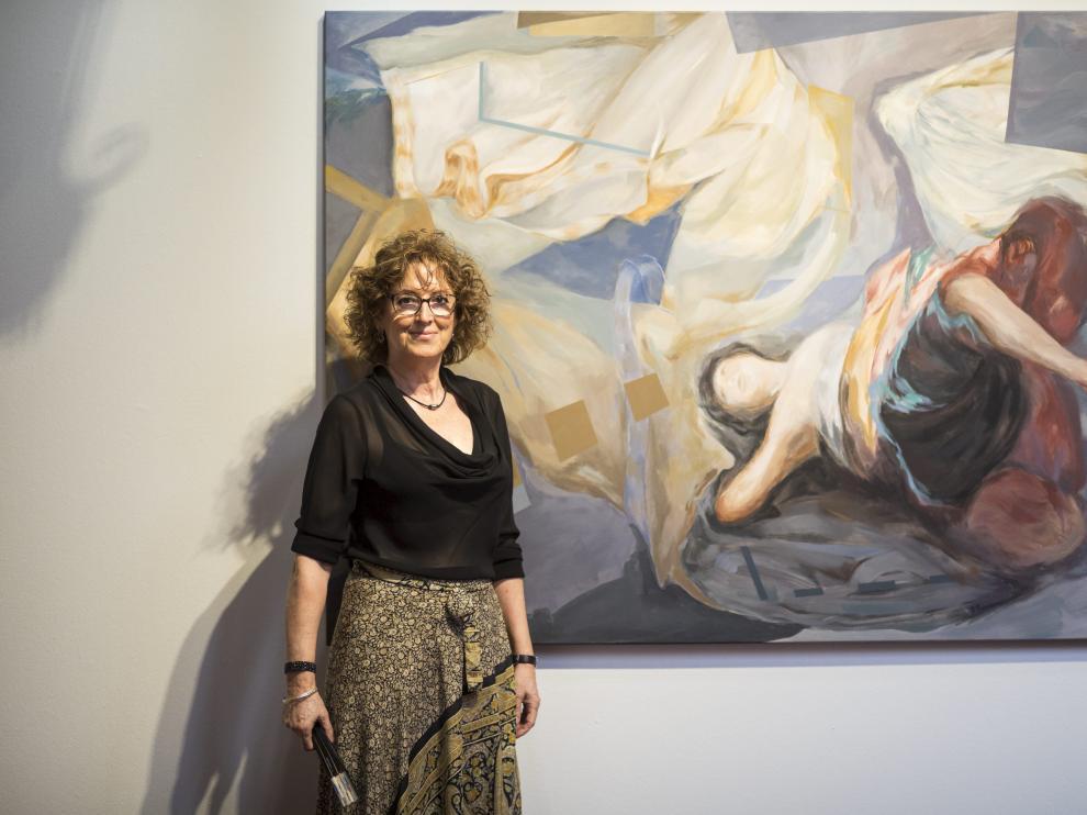 La pintora Carmen Pérez-Ramírez, ante sus obras, en la galería de arquillos del palacio de Sástago.
