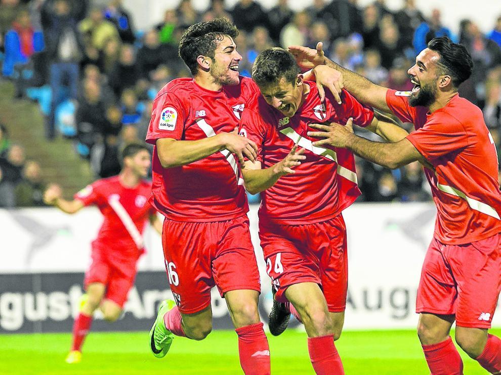 Marc Gual, en el centro, recibe la felicitación de dos compañeros del Sevilla Atlético tras marcar hace un año en La Romareda.