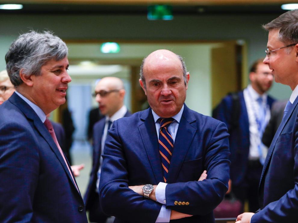 De Guindos, junto al presidente del Eurogrupo, Mario Centeno, y el vicepresidente de la Comisión Europea, Valdis Dombrovskis.