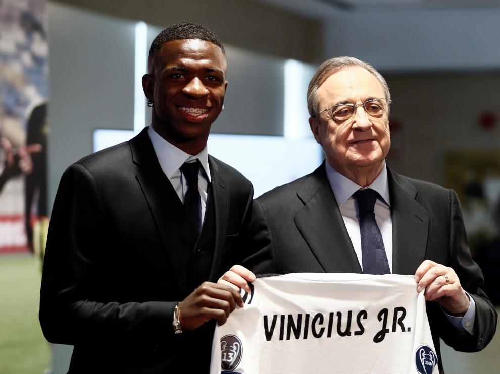 Vinicius Junior sujeta su nueva camiseta, sin dorsal, junto al presidente Florentino Pérez
