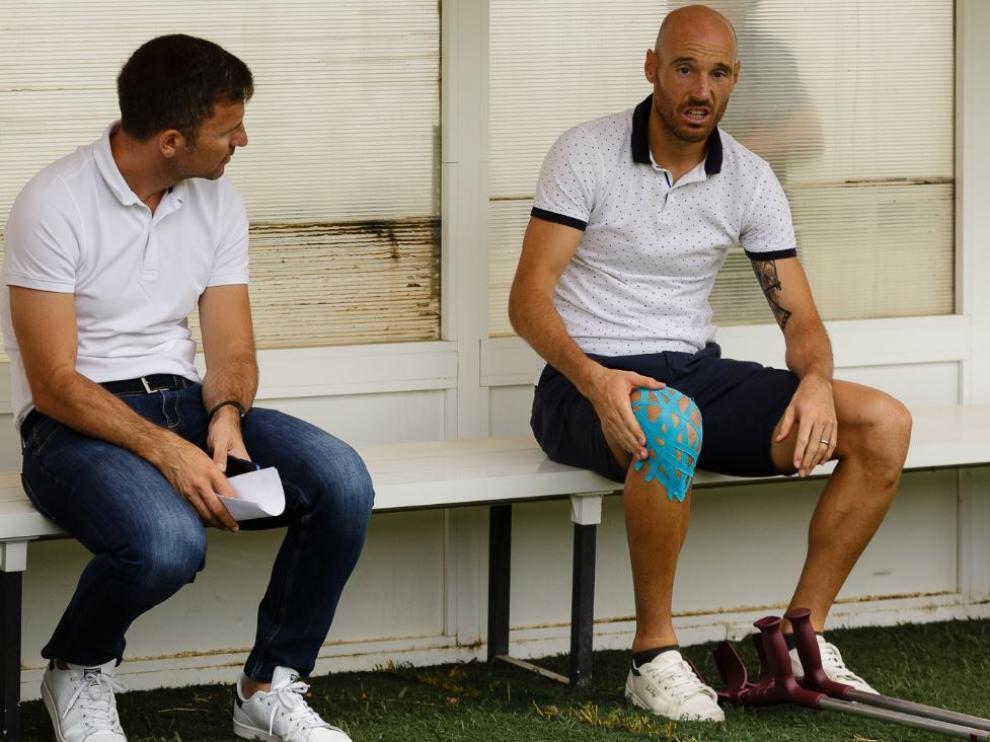 Toquero, con las muletas en el suelo y la rodilla dañada aún protegida, charla con el director deportivo Lalo Arantegui en el banquillo del campo del Tudelano, este sábado antes del partido amistoso del Real Zaragoza.