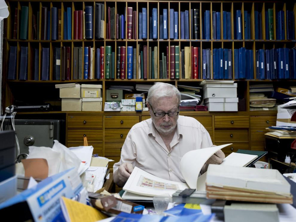 Manuel Duplá, dueño de la última filatelia de Aragón, revisa unos sellos en su despacho.
