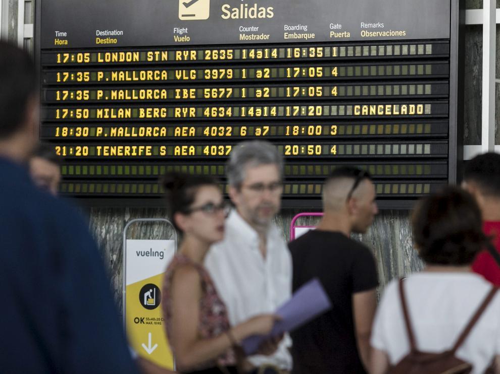 Un grupo de afectados, ayer ante el panel que anuncia la cancelación del vuelo a Bérgamo.