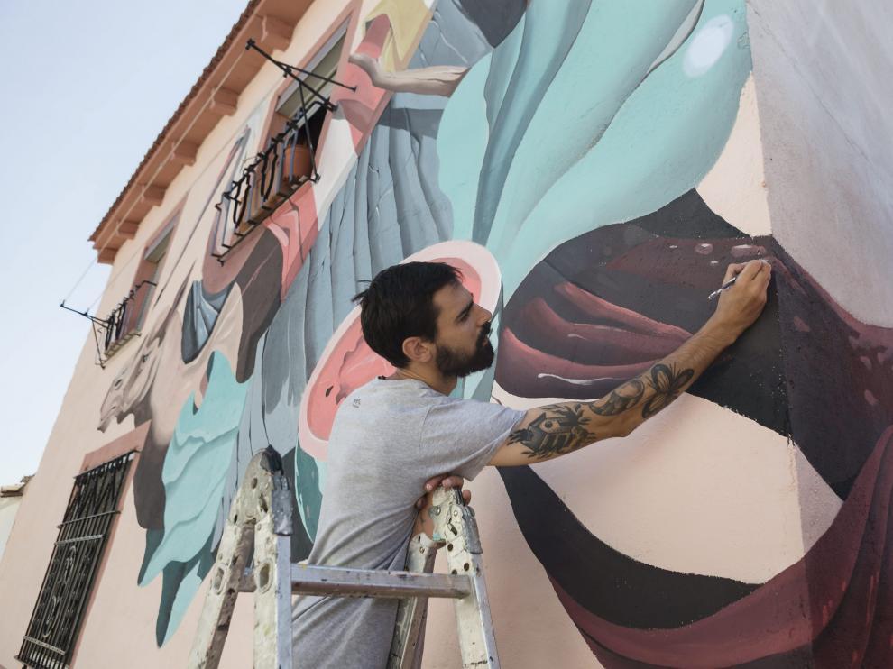 """Denis Galocha, del equipo Twee Muizen, repasa un detalle de su mural, una suerte de """"bodegón con animales""""."""